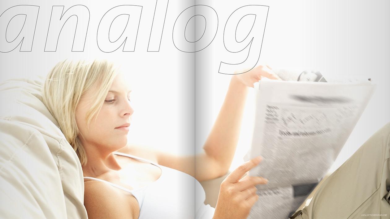 """Detail eines Doppelseitenlayouts mit Schriftzug """"analog"""": Eine Frau ließt in einer Zeitung"""