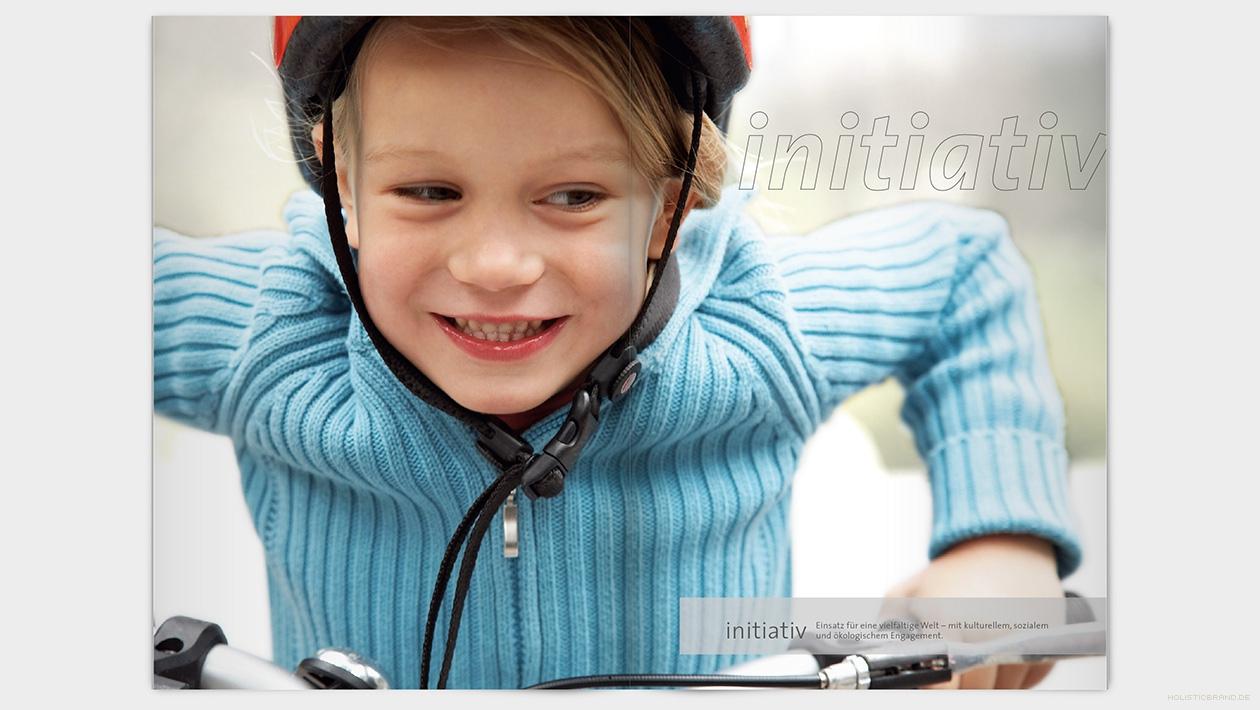 """Layout einer Doppelseite mit Schriftzug """"initiativ"""": Großansicht eines Kindes auf einem Fahrrad"""
