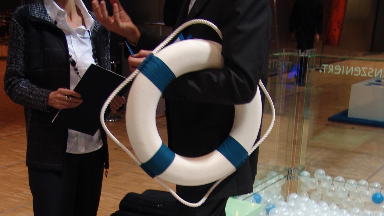 Detailfoto eines Gesprächs zweier Geschäftsleute am Stand, eine Person hat einen Rettungsring im Arm