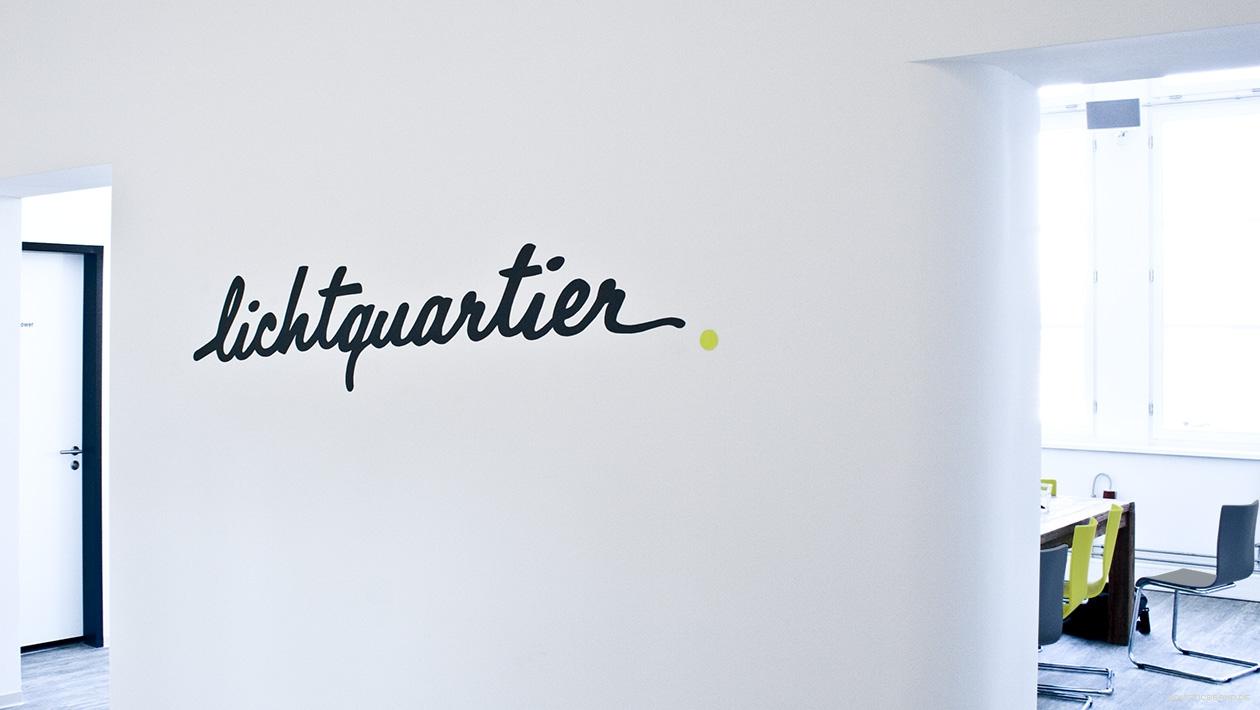 Fotografie einer Wand mit Logoschriftzug und Durchgang zum Studio