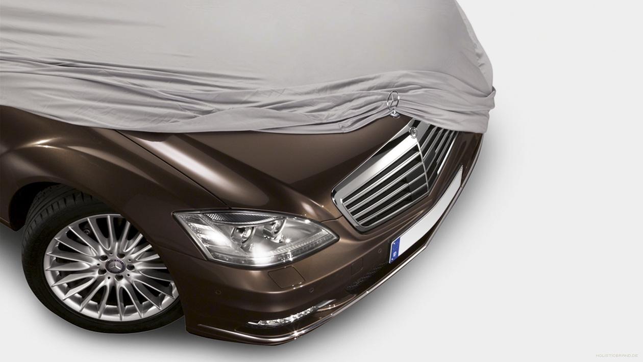 Fotografische Bildkomposition einer von einem Tuch halbenthüllten Mercedes-Benz-Motorhaube