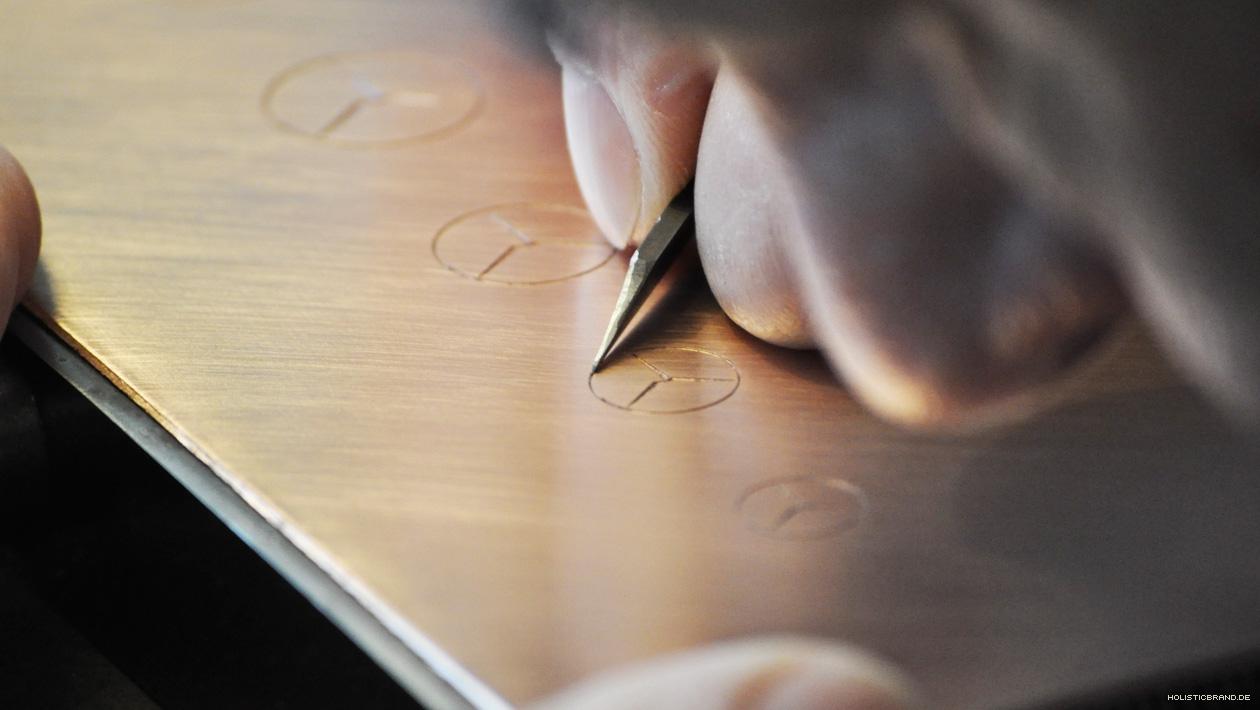 Detailfoto eines Graveurs bei der Arbeit an einer Druckform